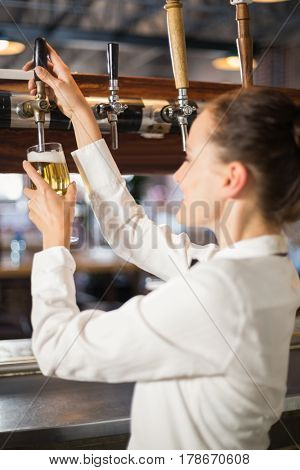 Beautiful barmaid pouring a beer in a bar
