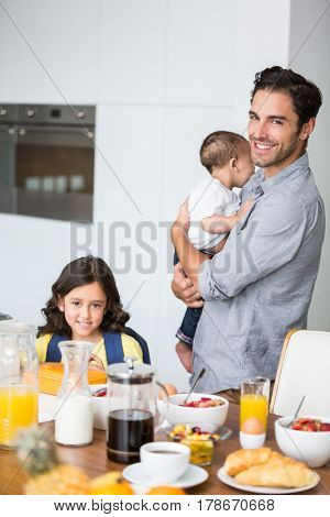 Portrait of smiling father and daughter with baby at breakfast table in home