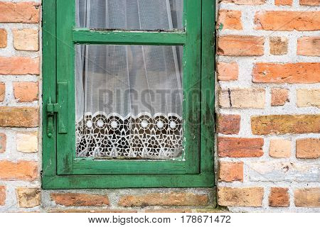 Green painted old cracked window with white lace curtains. Detail of vintage decor