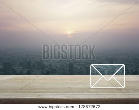 Mail icon on wooden table over city tower at sunset vintage style Contact us concept