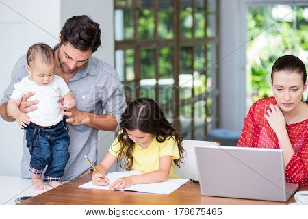 Mother using laptop daughter doing homework with father at home