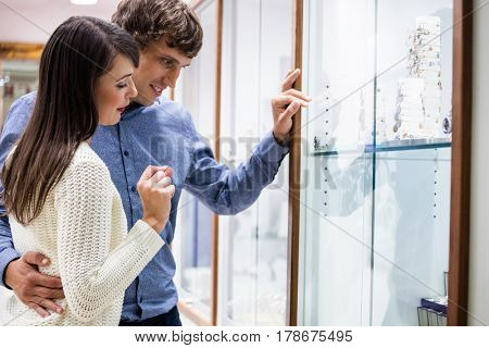 Happy couple looking at display while shopping in jeweler shop