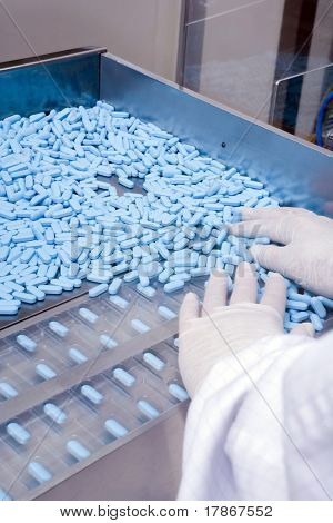 Blue pills being produced in a pharmaceutical facility