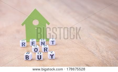 RENT OR BUY word of cube letters in front of green house symbols on wooden surface. Concept.