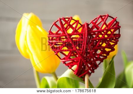 yellow tulips and handmade red heart on wooden background