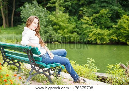 Young woman in white shirt sitting on the bench near the pond in the park