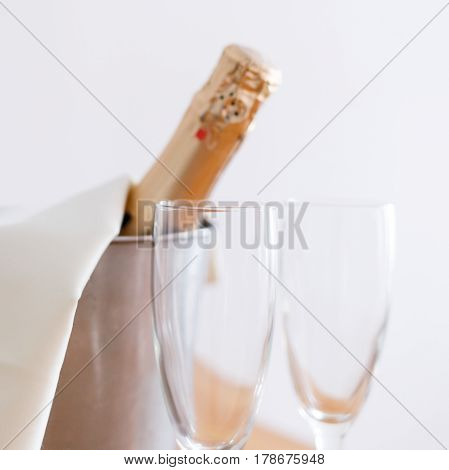 Champagne bottle in bucket and two empty glasses standing against white wall