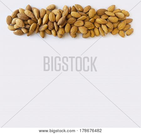 Almonds at border of image with copy space for text. Kernels almonds on a white background. Top view. Vegetarian or healthy eating. Background of almond.