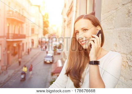 Young european woman calling phone standing on balcony and looking on street