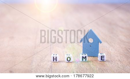 HOME word of cube letters in front of blue coloured house symbol on wooden surface.