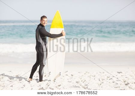 Happy man holding a surfboard on the beach at sunny day