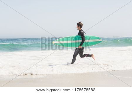 Man in wetsuit carrying a surfboard and running towards sea