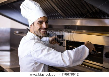 Handsome chef preparing grill in a commercial kitchen