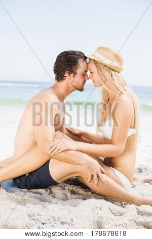 Young couple sitting face to face and romancing on the beach