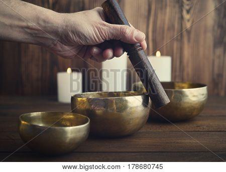 Male Playing On Tibetan Singing Bowls