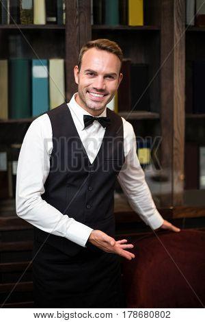 Handsome waiter welcoming client in a fancy restaurant
