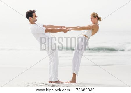 Romantic couple holding hands and bending backwards on the beach