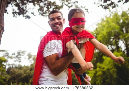 Father and daughter pretending to be a superhero in park