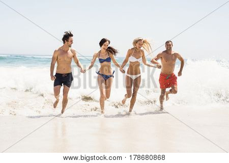 Happy friends holding hands and running on the beach on a sunny day