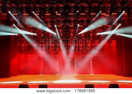 Illuminated concert stage without people with red light and stage fog