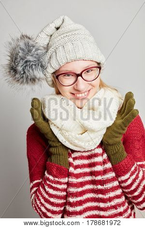 Smiling woman with glasses wearing a cap and a scarf in winter