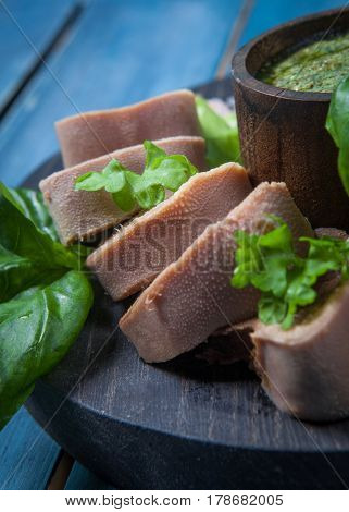 Boiled beef tongue on dark wooden table with pesto and salad