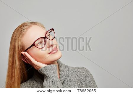 Young blond woman daydreaming looking up