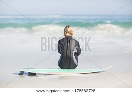 Rear view of woman in wetsuit sitting with surfboard on the beach on a sunny day