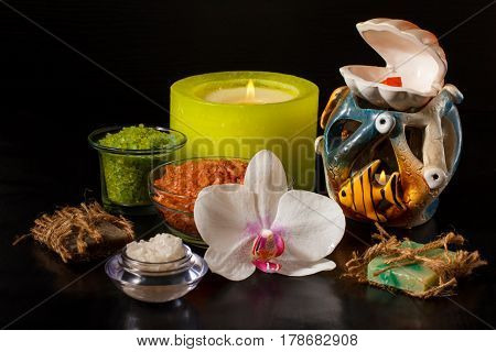 Spa products with white orchid flower handmade soap bowls with sea salt candles on black background