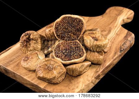 Dried figs on wooden chopping board and black background