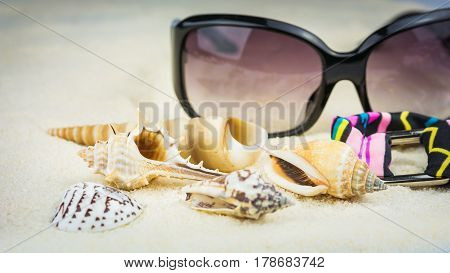 Summer holiday theme with sea shells, sunglasses and swimsuit with ethnic ornament on sandy beach.