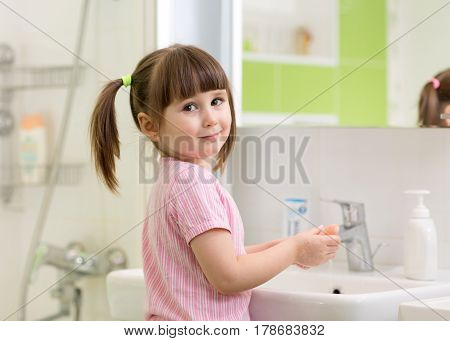 Cute kid girl with ponytail in pink bathrobe washing her hands with soap.