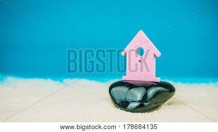 Symbol of little lilac house secured builed on black stone on blue background.
