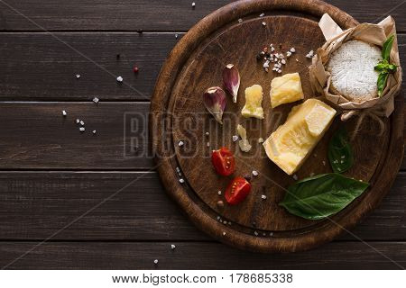 Wooden desk with parmesan, camembert and brie cuts decorated with garlic, tomato and basil, top view, copy space. Cheese delikatessen on rustic wood.