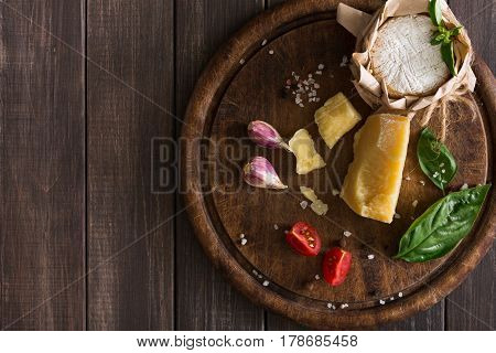 Cheese delikatessen on rustic wood. Wooden desk with parmesan, camembert and brie cuts decorated with garlic, tomato and basil, top view image with copy space