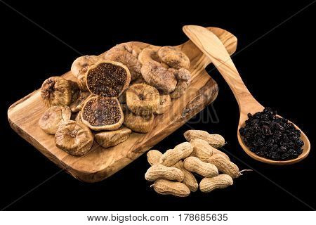 Dried figs on wooden chopping board, peanuts and black raisins in wooden spoon on black background