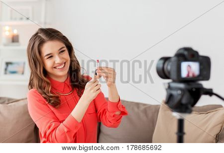 blogging, technology, videoblog, makeup and people concept - happy smiling woman or beauty blogger with lipstick and camera recording tutorial video at home