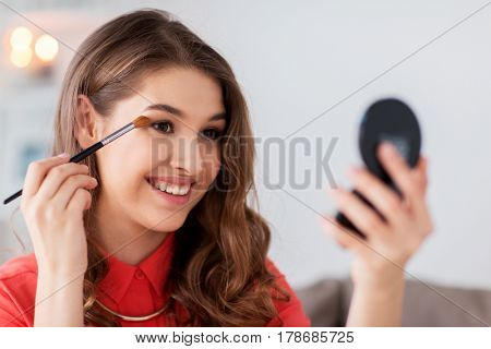 beauty, makeup, cosmetics and people concept - happy smiling young woman applying eyeshade with eye shadow brush and looking to mirror at home