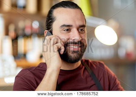 small business, people and service concept - happy man or waiter in apron calling on smartphone at bar