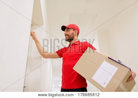 delivery, mail, people and shipment concept - happy man in red uniform with parcel box in corridor knocking on door