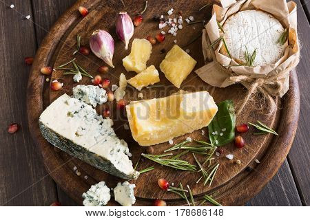 Cheese delikatessen closeup on rustic wood. Wooden desk with blue cheese roquefort, parmesan, camembert and brie cuts decorated with garlic, pomegranate and rosemary.