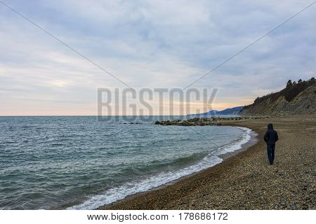 The man in the jacket is on the shore of the black sea.