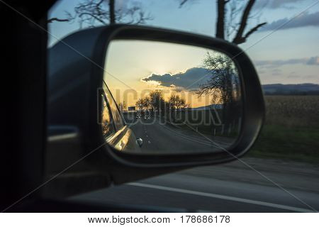The reflection of the sunset in the automotive rearview mirror