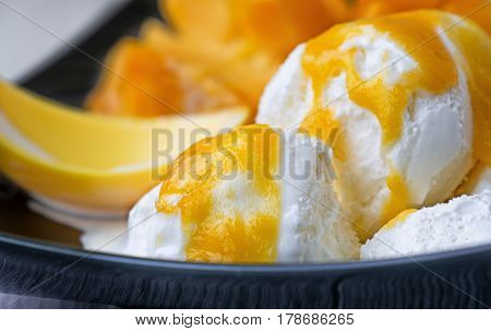 white ice cream with a sauce of ripe mango fruit with yellow folding spoon for ice cream