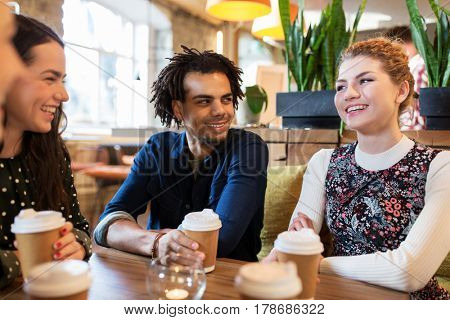leisure, drinks, people and communication concept - happy friends drinking coffee from disposable paper cups at restaurant or cafe