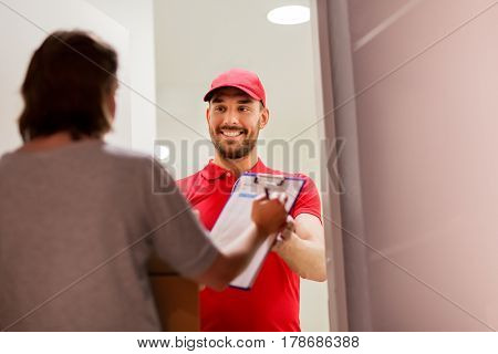 delivery, mail, people and shipping concept - happy man delivering parcel boxes and customer signing form on clipboard at home