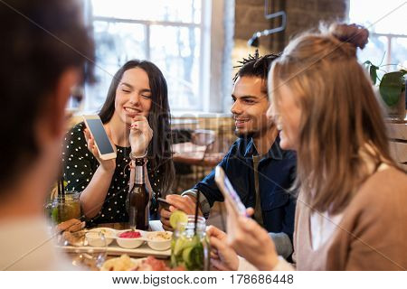 technology, lifestyle and people concept - happy friends with smartphones taking picture of food at bar or cafe