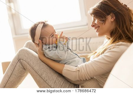 Young mother holding her baby girl in her arms sitting on a living room couch next to a window laughing and playing. Focus on the baby