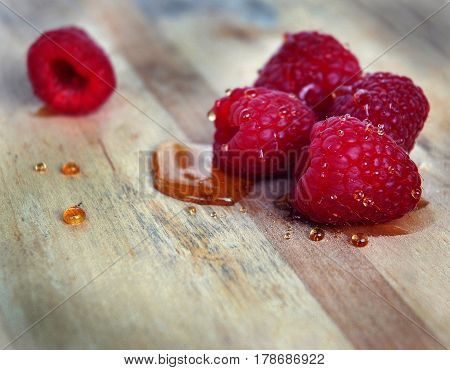 Raspberries closeup on a wooden Board. Beautiful background with raspberries. raspberries with honey on wooden background.