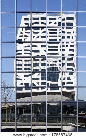utrecht 15march 2017: new city office utrecht seen from footbridge reflected in glass building of rabobank